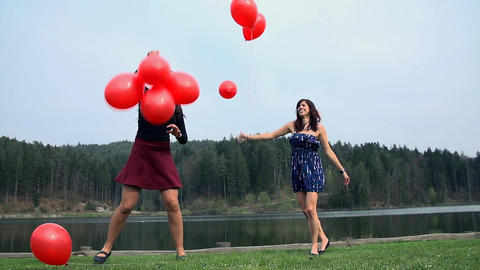 Two Older Girls Enjoying Playing With Red Balloons stock footage