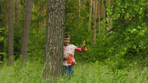 Happy child hiding behind a tree in the forest Footage
