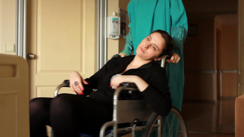 nurse carrying patient on a wheelchair 2 Stock Video Footage