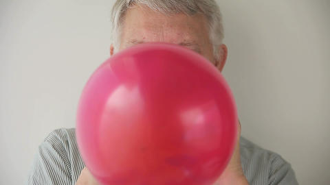 man blows up and ties balloon Footage