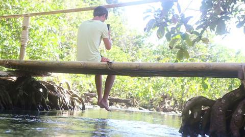 man sitting on the bridge with his legs dangling u Footage