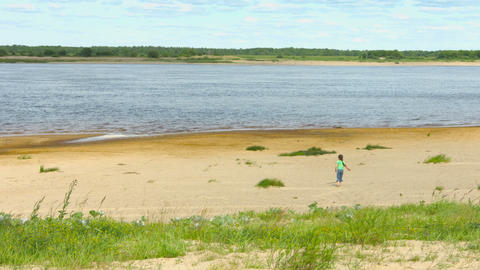 Lonely child walking along the shore of a large ri Footage