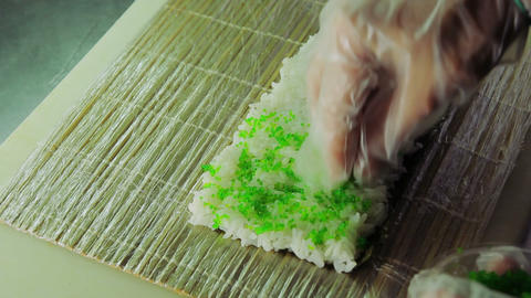 Cook adding green tobiko to sushi rolls Footage
