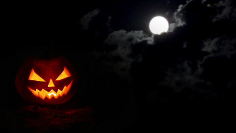 Halloween pumpkin at night and moon in clouds Footage