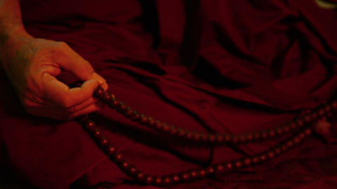 Rosary in hand of the monk meditating in a dark ro Footage
