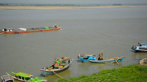 Barge transporting goods by river near small boats Footage