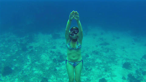 Girl pops up after a deep dive in the sea. Show th Footage