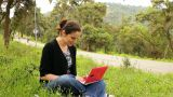Beautiful Girl Using Computer In Countryside, Bicycles Passing Behind stock footage