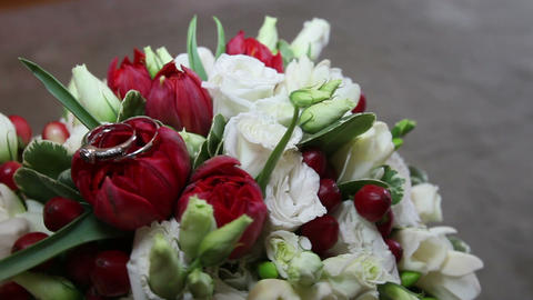 bouquet of red and white roses lays wedding rings Footage