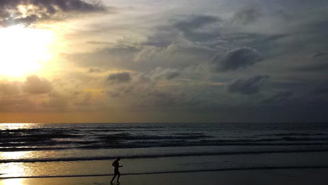 Silhouette of a man running on the beach at sunset Footage