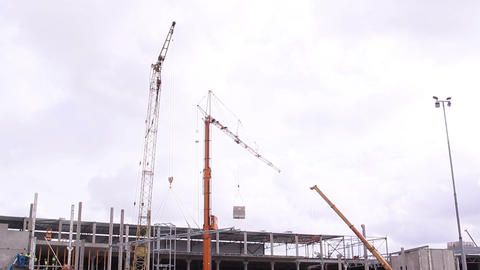 Three huge cranes loading off some construction ma Footage