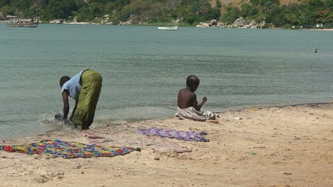 Malawi: poor people washing loundry in a lake Stock Video Footage