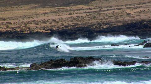 dangerous surfing between lava rocks 2 Stock Video Footage