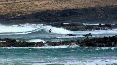dangerous surfing between lava rocks 2 Stock Video Footage