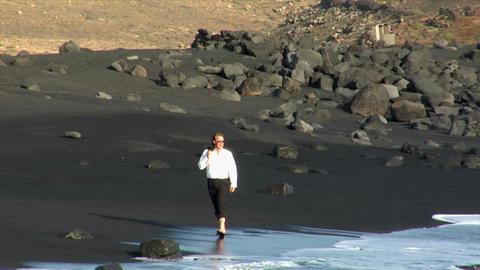 business man happy jump rock black beach Stock Video Footage