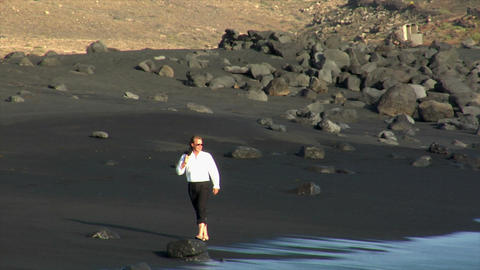 business man happy jump rock black beach Stock Video Footage