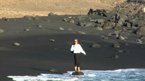 business man happy jump rock black beach Footage