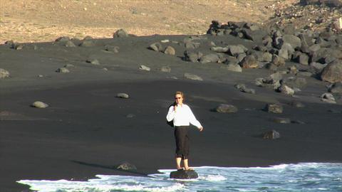 business man happy jump rock black beach Footage