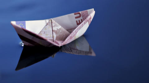 Boat made of Euro note afloat on blue water Stock Video Footage