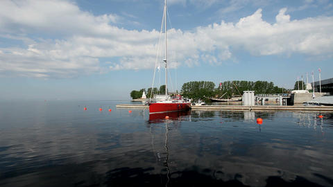 Red Sail Boat At The Pier In The Background Of Blue Sky stock footage