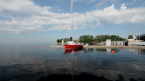 Red Sail boat at the pier in the background of blue sky Stock Video Footage