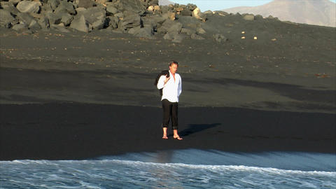 business man thinking walk water black beach Stock Video Footage