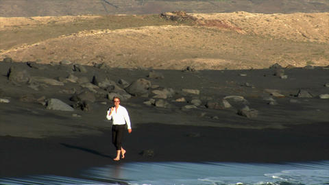 business man walk black lava beach Stock Video Footage