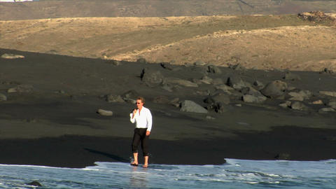 business man walk black lava beach Stock Video Footage
