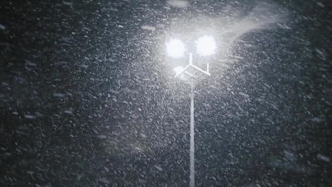 Snow falling in streetlight beams at night. Loop Footage