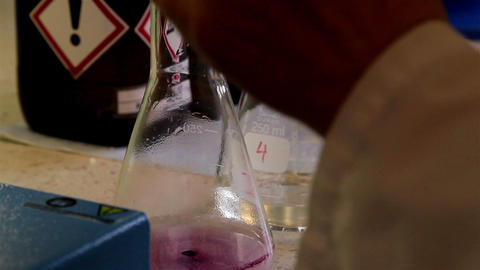 A laboratory technician putting chemicals in the f Footage