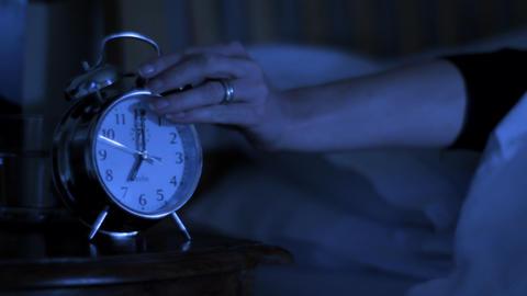 Woman woken up by alarm clock Stock Video Footage