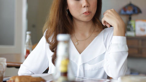 Beautiful woman drinking coffee and reading newspa Footage