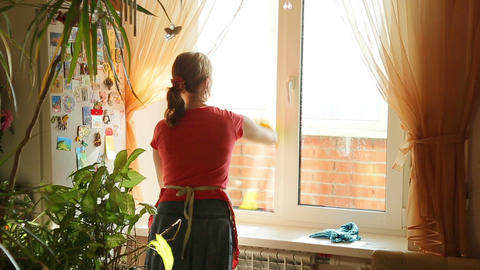 Girl washes the window , view from the back Live Action