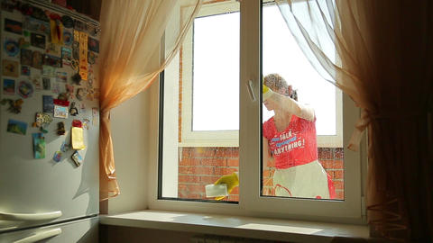 Girl washes the window , view from the front Live Action