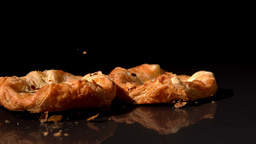 Pastry snack falling on black background Live Action
