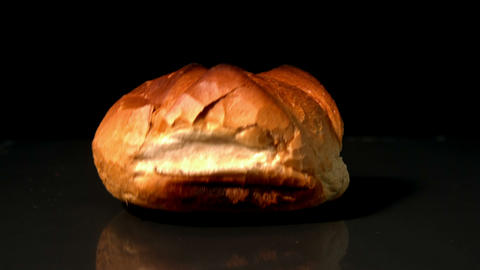 Loaf of bread falling on black background Footage