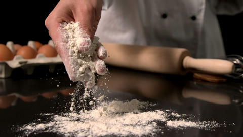 Chef Sprinkling Flour On Black Surface stock footage