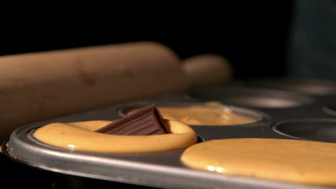 Chocolate square dropping into cupcake batter in tray Footage