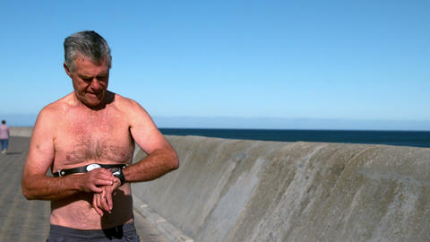 Senior man jogging shirtless on sunny day Footage