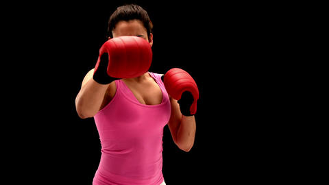 Fit young woman punching at camera on black background Footage