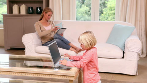 Cute little girl using laptop while mother uses tablet Footage