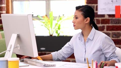 Pretty designer working at her desk on computer Footage