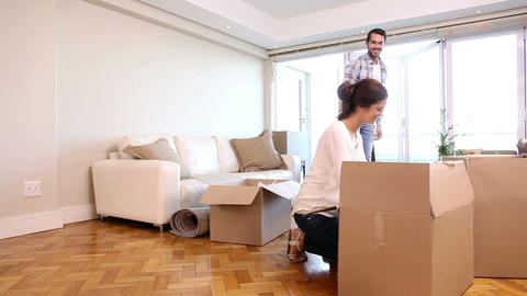 Attractive couple unpacking boxes in their living room Footage