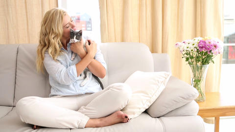 Happy blonde petting her kitten on the couch Footage