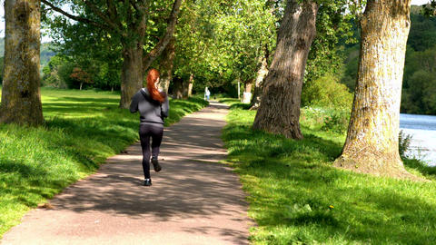Fit redhead jogging along path outside Footage