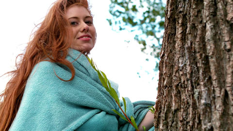 Pretty redhead wrapped in blanket by a tree Live Action