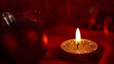 Gold glitter candle flickering beside bauble Footage