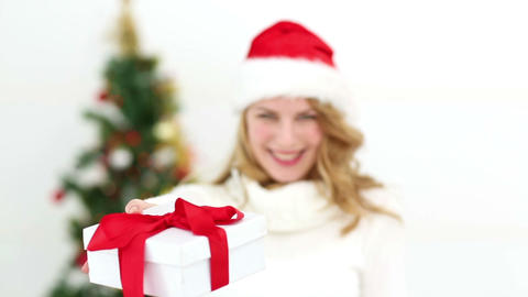 Festive blonde smiling at camera offering gift Footage