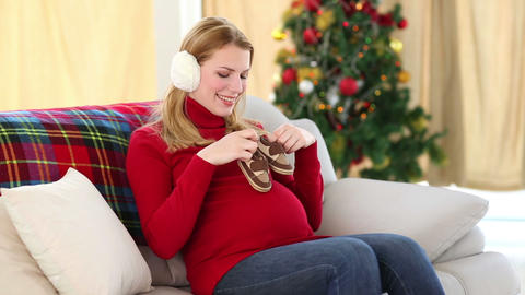 Festive pregnant blonde holding baby booties Footage