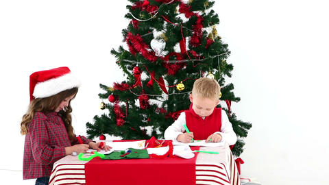 Cute Siblings Drawing By The Christmas Tree stock footage
